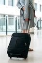 Woman with travel suitcase at international airport s legs and Royalty Free Stock Photo