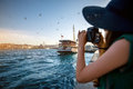 Woman traveler on the bosphorus in istanbul young green dress and hat enjoying great view of Stock Images