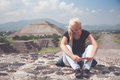 Woman traveler resting on the top after a long hard climb on one of famous ruins of ancient city Maya in Teotihuacan, Mexico wi