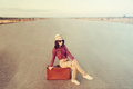 Woman traveler on road sits vintage suitcase travel theme with retro filter Stock Photography
