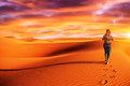 Woman traveling in the desert active trekking along walking alone dune discovering nature expedition to wilderness travel and Royalty Free Stock Photos