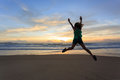 Woman traveller happy jumping on the beach with sunrise Royalty Free Stock Photo