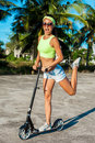 Woman travelling by scooter. Happy woman kick scootering on the beach near palms in tropical country. Royalty Free Stock Photo