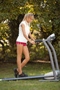 Woman on the treadmill exersising outdoors strange situation ideal for commercial Royalty Free Stock Image