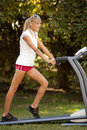 Woman on the treadmill running outdoors strange situation ideal for commercial Stock Photos