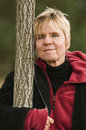 Woman with tree upper body portrait of a mature head on a looking embracing and in the camera Stock Photo
