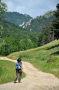Woman trekking on a winding dirt lane road ascending a mountain romania Stock Photos