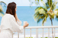 Woman on a tropical balcony in bath robe looking at beautiful ocean view from with morning coffee Royalty Free Stock Photography