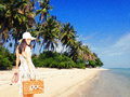 Woman on tropical vacation young with retro suitcase and shoes in hand Royalty Free Stock Photo