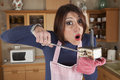 Woman trying to cook in a miniature oven humorous photo Stock Photo