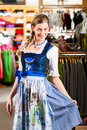 Woman is trying Tracht or dirndl in a shop Royalty Free Stock Photos