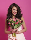 Woman with tulips in wavy hair holding spring bouquet Stock Photos
