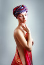 Woman in turban a photo of beautiful girl a head dress from the coloured fabric and red ethnic dress Stock Photos