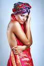 Woman in turban a photo of beautiful girl a head dress from the coloured fabric and red ethnic dress glamour Royalty Free Stock Photography