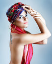 Woman in turban a photo of fashionable beautiful young a head dress from the coloured fabric and red ethnic dress Royalty Free Stock Photo
