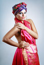 Woman in turban a photo of fashionable beautiful young a head dress from the coloured fabric and red ethnic dress Royalty Free Stock Images