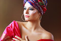 Woman in turban a photo of fashionable beautiful young a head dress from the coloured fabric and red ethnic dress Stock Image