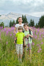 A woman and two boys stand on field of fireweed Royalty Free Stock Photo