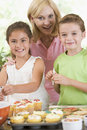 Woman with two children decorating cookies Stock Image