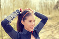 Woman tying hair in ponytail getting ready for run beautiful asian young adult attaching her long brown on outdoor trail Royalty Free Stock Photo