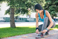 Woman tying her shoelace outdoors sports young Stock Photography