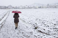 Woman with umbrella is strolling in the snow Royalty Free Stock Photography