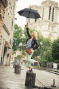 A woman with umbrella young like mary poppins pretending to fly in front of notre dame de paris Stock Photo