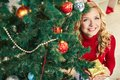 Woman under firtree smiling female with giftbox looking at camera out of decorated Stock Photo