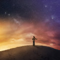Woman under night sky standing in snow starry Royalty Free Stock Image