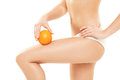 Woman in underwear holding an orange showing absence of ce young cellulite over white background Royalty Free Stock Images