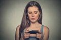 Žena nešťastný naštvaný podle něco někdo na její mobilní telefon textové zprávy