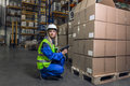 Woman in uniform holding device crouching