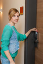 Woman unlocking door young beautiful the with a key card Stock Photography