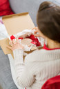 Woman unpacking parcel with Christmas gift Royalty Free Stock Image