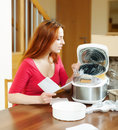 Woman unpacking and reading manual for new crockpot cheerful at home interior Stock Photo