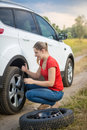 Woman unscrewing nuts on car flat wheel at field Royalty Free Stock Photo