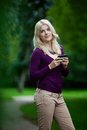 Woman updating status on cell phone looking over shoulder while using in park Royalty Free Stock Images