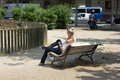 Woman use of cellphone while seating in park in old town Royalty Free Stock Photo