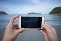 Woman use smart phone take a photo of the sea in Prachuapkhirikhan ,thailand real picture in monitor Royalty Free Stock Photo