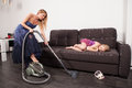 Woman use vacuum cleaner young women in evening dress little girl lying on sofa Stock Photo