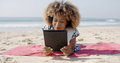 Woman Uses A Tablet On The Beach Royalty Free Stock Photo
