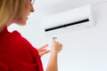 Woman using air condition with remote control Stock Images