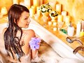 Woman using bath sponge in bathtub. Stock Image