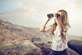 Woman using a binoculars looking at something with at the mountains Royalty Free Stock Images
