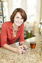 Woman using cell phone at home smiling mature mobile in kitchen Stock Photography