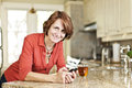 Woman using cell phone at home smiling mature mobile in kitchen Royalty Free Stock Images