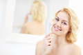 Woman using face cleansing brush a picture of a young in the bathroom Stock Images