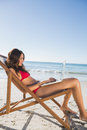 Woman using her laptop while relaxing on her deck chair the beach Royalty Free Stock Photo