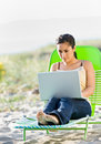 Woman using laptop at beach Royalty Free Stock Image