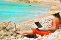 Woman using laptop on the beach Royalty Free Stock Image
